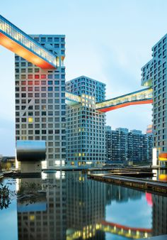 Beijing, The Linked Hybrid bridges harness color and under-lighting to animate and reflect off the pool below. The eight enclosed bridges connect eight buildings at slightly differing levels and with varying interactions