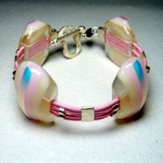 Designer Pink Glass Bracelet by Jan Art  Israel.This high fashion art glass bracelet is constructed from 4 large fused glass stones, pink silk cords and sterling silver spacers.  The bracelet features a mix of soft colours including pink, blue and cream. An original from jewellery designer Jana Sobelmann of JanArt.