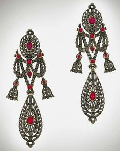 A pair of early 19th century ruby and diamond pendent earrings   Each oval openwork surmount centrally-set with a cushion-shaped foil-back ruby and accented with old rose-cut diamonds all in closed-back settings, suspending a similarly-set garland and pear-shaped pendant, circa 1810, 10.5cm long, possibly Catalan