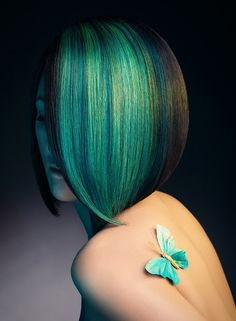 A Women with a butterfly on her body... gives her hair colors in beautiful aqua shades...