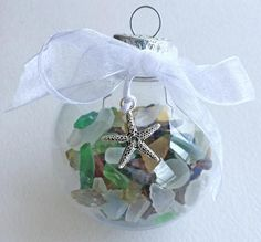 FEATURED ON COMPLETELY COASTAL! One of our best sellers! Our Sea Glass Ornaments add a special beachy touch to any coastal Christmas tree. Beautiful shards of white, blue, green, turquoise and amber tumbled glass are encased in the highest quality acrylic ornament balls. The ornaments look just like glass, but wont break at home or during shipping! NEW THIS YEAR: • Optional beachy dangle charm. See photo 2: left to right, mermaid, starfish 1, sand dollar, starfish 2, flip flop, scallop…