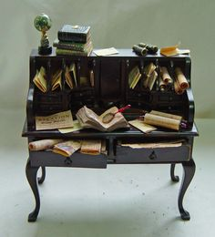 UNIQUE MINIATURES - THE ADVENTURER DESK. This is an excellent quality JiaYi Desk. The colour of the wood is very very dark mahogany, almost black in colour with the edges aged. All the papers etc. are handmade by Artisan Janet Dowling. Everything is fixed in place.