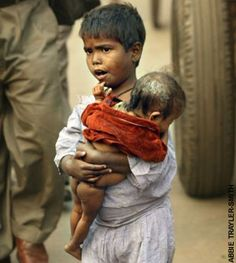 Poor child carried by his brother