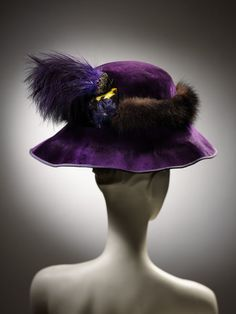 Hat from Woolland Bros. (retailers) | Made in London, circa 1910 | silk plush trimmed with fur and feathers | royal purple plush millinery hood with black mink or sable fur band, spray of purple feathers and purple and yellow parrot's head | Via VA Museum, London.