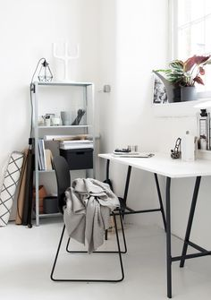 white workspace with black details and green plants black muuto chair