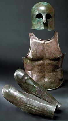 Greek set of armour: a Corinthian helmet, 7th century B.C., a muscle armour breastplate, 5th century B.C. and a pair of greaves, 5th century B.C.