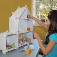 Eco friendly Mod House by Urban Canvas: build-able, portable dollhouse made of cardboard panels, movable walls, connectors and furniture. Entire set has a crayon-erasable surface.