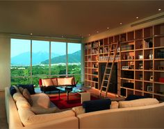 A living room with a massive wall of shelving around the entertainment center, complete with a rolling bookcase ladder. The seating consists of a large L-shaped beige sectional and a red and black loveseat.
