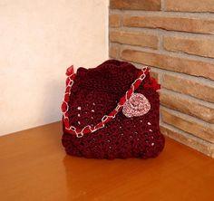 Pochette realizzata ad uncinetto decorata con catenina, nastrino e rosa