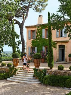 Fekkai and Von Wulffen with their children Philip and Cecilia on the entrance-court steps, which are flanked by boxwood in monumental Anduze pots. The house's façade features a traditional Provençal ocher finish and gray shutters.