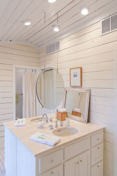 White wood walls with a suspended mirror. #beach #house #decor