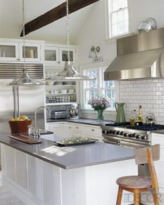 White kitchen with gray counter top,  Stainless steel appliances, &  hanging  lamps