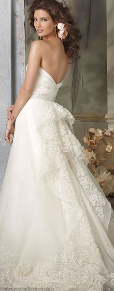 Delicately detailed ivory silk organza A-line wedding gown with strapless draped bodice, embroidered cascade back, and chapel-length train from Jim Hjelm Bridal Couture....