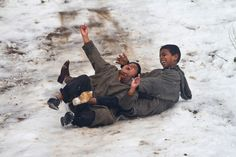 Kashmiri boys play in the snow in Srinagar, India, on Jan. 19. Snowfall in the Indian portion of Kashmir has disrupted power supply and road traffic between Srinagar and Jammu.