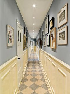 hallway design ideas, long narrow corridor, pale blue-grey walls, with cream white paneling, and many framed images, white ceiling with inbuilt lights, tiled floor and white doors #hallwayideasnarrow