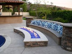 Warm up your patio or deck with a dramatic outdoor fireplace. Designer Scott Cohen of The Green Scene creates a fire trough featuring brilliant blue stones for a splash of color. A built-in bench made of concrete with a stucco veneer. Diy Fire Pit, Fire Pit Backyard, Backyard Patio, Backyard Landscaping, Fire Pits, Landscaping Ideas, Backyard Seating, Patio Ideas, Backyard Ideas