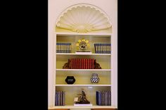 President Obama's bookshelf in the Oval Office features both natural and technical objects. Two pieces of pottery by contemporary Native American sculptors stand on one shelf, while patent models occupy the top and bottom shelves. On the top shelf lies Henry Williams' 1877 patent model for his feathering paddle-wheel for steamboats; the bottom shelf holds John A. Peer's 1874 patent model for a gear-cutting machine.
