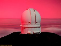 Canada-France-Hawaii Telescope painted in pink by a dramatic sunset at the summit