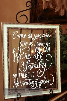 "Gold and white framed ""Come as you are, stay as long as you can, we're all family, so there is no seating plan"" sign welcomes guest to the reception 