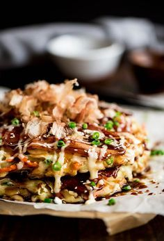 Okonomiyaki - Delightful savory Japanese pancakes made from an easy to make batter, cabbage and bacon topped with Japanese mayo and okonomiyaki sauce.    curiousnut