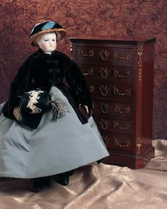 """Theriault's Antique Doll Auctions - French Bisque Poupee Marked B.S. -  Attributed to Blampoix, circa 1862. Along with a French Walnut Chest with Bronze Fittings - 15""""H.   The furniture was sold at the prestigious store Maison Giroux. Circa 1865."""