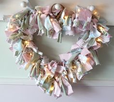 How to make a heart shaped rag wreath out of just a wire coat hanger and some old baby clothes.  Add a bit of girlie bling with some fairy lights.