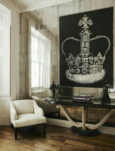 Classic chair n side console with a hanging painting of crown with mirrored wall a true classic side wall