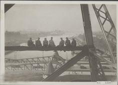 """De heftorens van de spoorbrug over de Koningshaven te Rotterdam worden geschilders. De schilders poseren voor de fotograaf. Op de achtergrond drie stoomschepen van de Holland-Amerika Lijn; de """"Rotterdam"""", de """"Statendam"""" en de """"Veendam"""" Datum oktober 1932 Locatie Rotterdam, Zuid-Holland Fotograaf Veld, K. in 't Nationaal Foto Archief"""