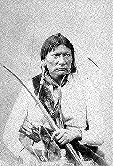 Milky Way (Asa Havi, Bird Chief), a Penateka Comanche; half-length, seated, holding bow.  Photographed by Alexander Gardner, 1872.