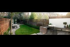 Nice combo of deck, grass, and cement. Fantastic, modern take on a privacy fence.