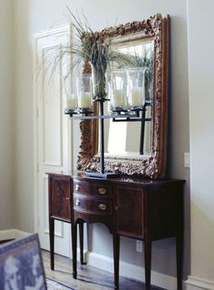 Love the tailored, formal mahogany console juxtaposed with the large, ornate gold mirror. The ornamental grass and large candle holder add a nice texture, but the candle holder would be too large and impractical on a console in my house, because it would take up too much space.