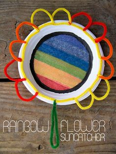 A little paint, a lot of pipe cleaners, and a paper plate makes this colorful Rainbow Flower Suncatcher Craft for kids!