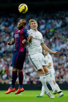 Toni Kroos of Real Madrid CF and Daniel Alves of Barcelona compete for the ball during the La Liga match between Real Madrid CF and FC Barcelona at Estadio Santiago Bernabeu on October 25, 2014 in Madrid, Spain.