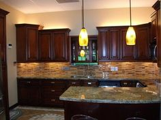 cherry cabinet kitchen and really like back splash combo with light granite  counter.