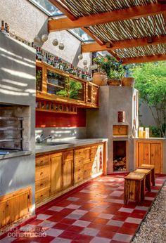 Com piso de ladrilho hidráulico (Ornatos), a área da churrasqueira também conta com forno de pizza e está integrada à cozinha. Sustentada por toras de jacarandá, a cobertura mescla vidro a ripas. Projeto de Sandra Sayeg.