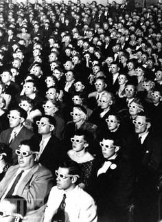 3-D Movie Audience: Photo by J.R. Eyerman, 1952.  J.R. Eyerman's peek inside the opening-night screening of Bwana Devil, the first full-length color 3-D feature, certainly is peculiar: Men and women, young and old all angle in the same direction, formally dressed but for those silly specs over their eyes. Funny as it is, with the audience members coming off like clones of an alien species, there's also prescience in the photo -- not just about the emergence of special effects in cinema but…