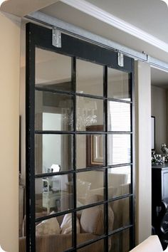 A salvaged window attached to barn door hardware to create a separation between entry and DR. (note barn door hardware; also, what about using a mirror behind it)