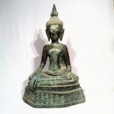 Bouddha maravijaya assis en virasana, les mains en bhumusparsa mudra, position de prise de la terre à témoin. Sa tête est surmontée d'un important ushnisha signe de grande illumination. Une dédicace chinoise est inscrite sur la base. Très originale sculpture en bronze à la cire perdue, ayant appartenu à une communauté chinoise du Laos. Laos XVI-XVII eme. Ht: 74 cm.