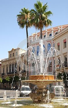 Photo made in Jerez of Frontera in Spain. In the photo, made in the city center, it is seen in the foreground a beautiful fountain, past the fountain and its jets of water you see two tall palm trees twins and some elegant palaces.
