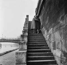 A courting couple kissing on the steps on the bank of the river.
