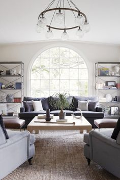 Bright living room with a retro chandelier, a set of armchairs, and a gray sofa