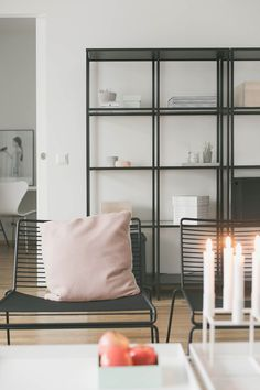 Black Hay Hee chairs, pink pillow, industrial style shelves.