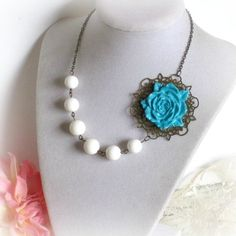 Vintage style handmade necklace starts of w/ a beautiful blooming turquoise flower that I sculpted using polymer clay. Followed by white shell pearls in 12mm and 10mm, a lovely chain in antique gold finish, and a clasp for closure at the back.