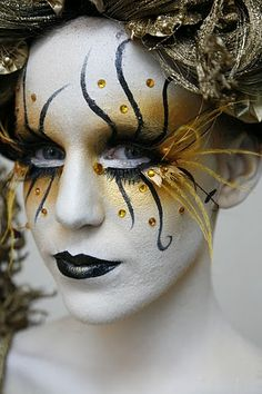 Artistic gold and black fantasy make-up look with topaz crystal accents.