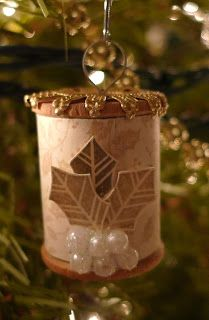 Sleepy in Seattle-Found a large bag of wooden spools at the local thrift shop and made my first ornament with a medium sized one. Simply cover it in designer paper, cut out some Stampin' Up! holly leaves in Crumb Cake from an older set, added pearls and Dazzling Diamonds. For the hanger, I flattened out an ornament top and curled it around the spool to secure.