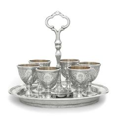 A VICTORIAN SILVER EGG-CRUET FROM KING GEORGE I OF THE HELLENES' BANQUETING-SERVICE MARK OF ROBERT GARRARD, LONDON, 1863  Circular base chased with floral sprays, with a central reeded scroll handle, with supports for the six egg-cups, the base engraved with Greek initials below Greek Royal crown, marked on base and cups The initials are those of King George I of the Hellenes, Prince of Denmark (1845-1913).  Christie's.