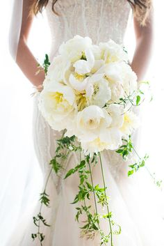 Cascading wedding bouquets bring elegance to your bridal look. Love this classic arrangement with lush white roses and peonies. {Photo courtesy of Callawaygable}