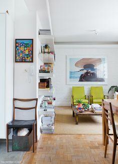 Sala de estar iluminada conta com uma seleção de móveis vintage, rústicos e peças de arte popular brasileira.