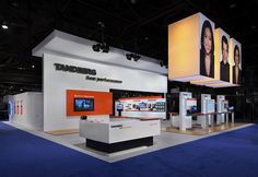 The design for this custom trade show exhibit was slick and clean. A sophisticated white-on-white palette incorporated giant fabric cubes visible from throughout the show floor with  eye-catching cool blue lighting. A silver puck system with an open inner core for wire management enabled the company to use 60 monitors in their large, 50' x 60' space without one visible wire.  MG Design: Trade Show Exhibits, Events, Environments, Experiences.  www.mgdesign.com