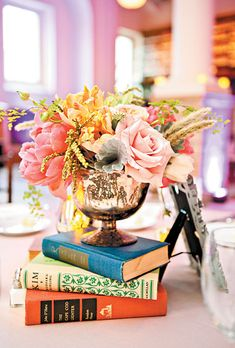 Brides.com: Simple Floral Wedding Centerpieces. Coral Peonies Atop a Stack of Books. A wedding centerpiece of coral charm peonies, Juliet garden roses, Quicksand roses, parrot tulips, poppy pods, and maidenhair ferns gets an unexpected upgrade when arranged on a stack of hardcover books.  See more peony wedding flowers.